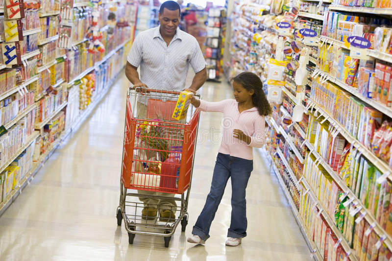 Father and daughter shopping in supermarket stock image