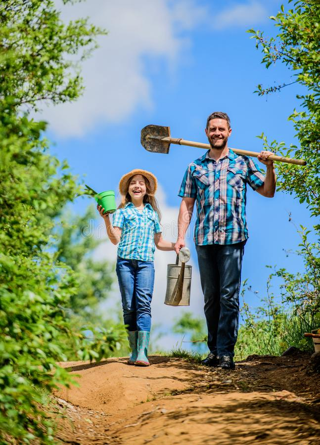 Father and daughter with shovel and watering can. Spring gardening checklist. It is time to plant prepare beds and care stock photo