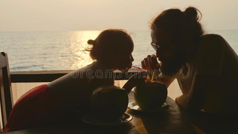 Father and daughter sits at seaview cafe and drinks coconuts together. Silhouette of father with cute little daughter sits at seaview cafe and drinks coconuts stock photo