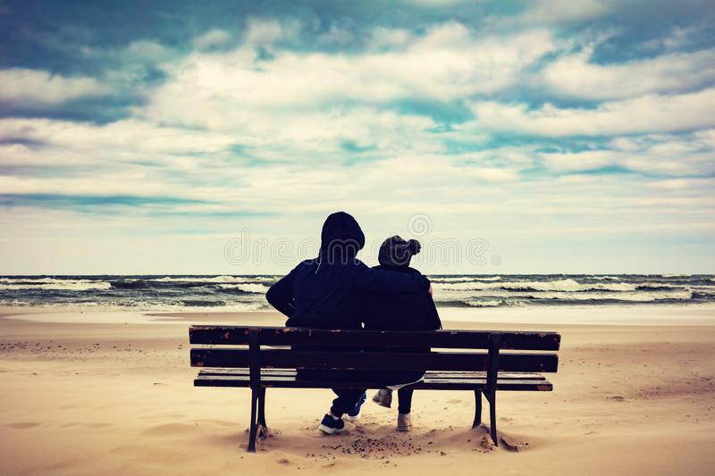 Father and daughter sitting on a bench on the beach royalty free stock photos