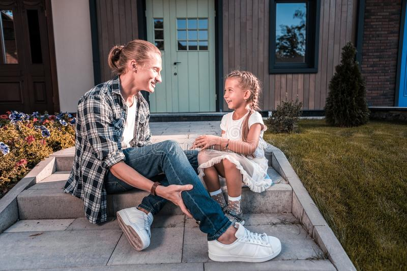 Father and daughter sitting on the porch outside house waiting for mother. Waiting for mother. Blonde-haired father and cute daughter sitting on the porch stock image