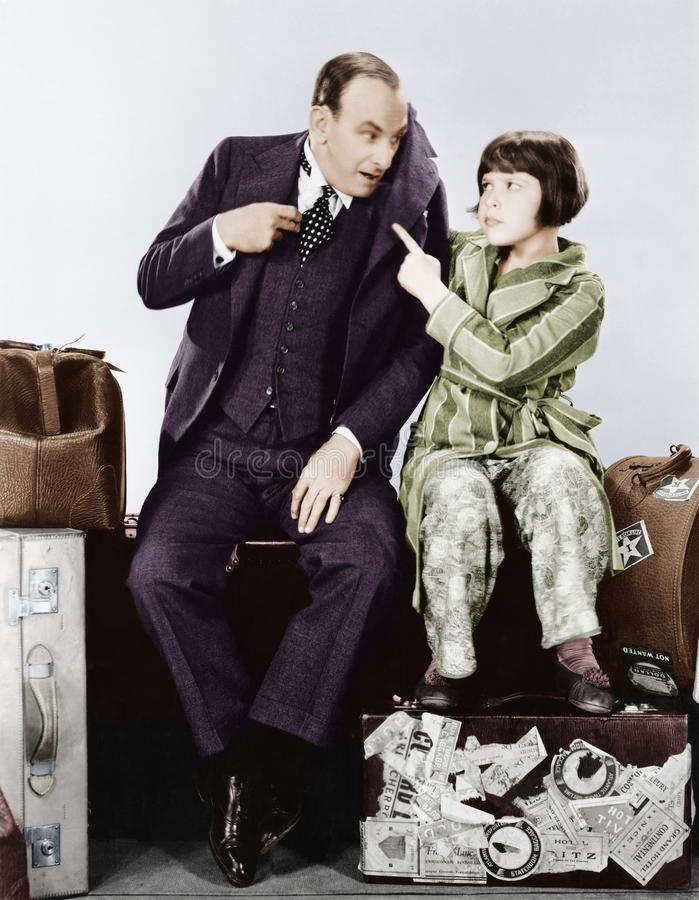 Father and daughter sitting together on luggage royalty free stock images