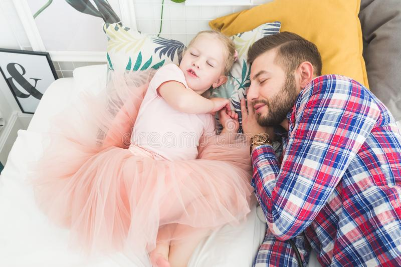 Father and daughter sleeping together in bed. royalty free stock image