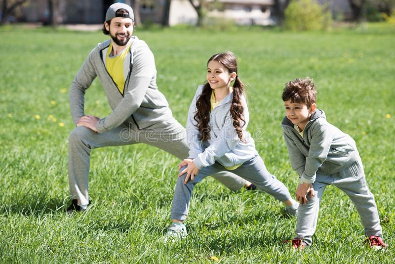 father with daughter and son doing physical exercise on grassy meadow royalty free stock photography