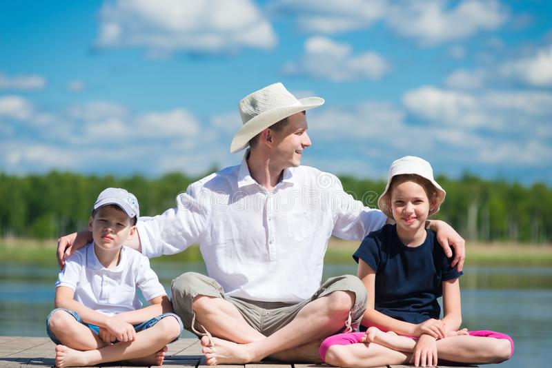 Father with daughter and son sits on a beautiful pier on the lake. Father with daughter and son sits on a pier on the lake royalty free stock image