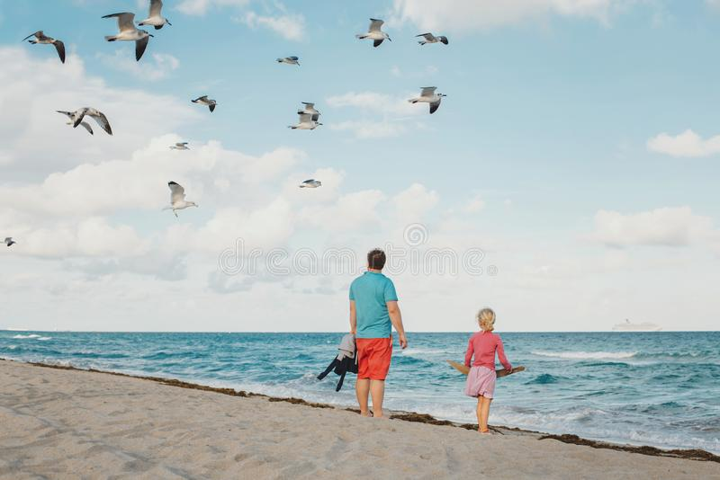Father and daughter standing on sea ocean beach and watching seagulls in  sky. Dad and child girl travelling spending time. Father and daughter standing on sea royalty free stock images