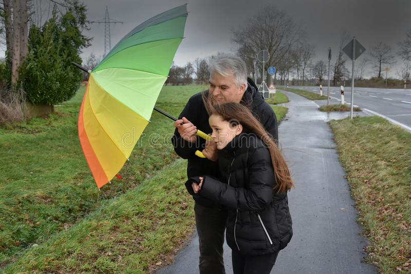 Father and daughter in stormy weather royalty free stock image