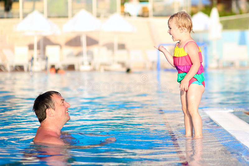 Father and daughter swimming in outdoors pool. Happy family, active father with little child, adorable toddler girl, having fun together in outdoors swimming royalty free stock photography
