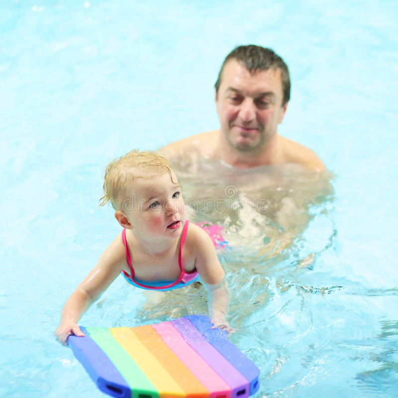 Father and daughter in swimming pool royalty free stock photography