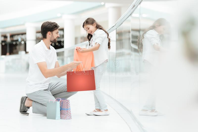 Father and daughter are taking out new sweater in shopping mall. royalty free stock photography