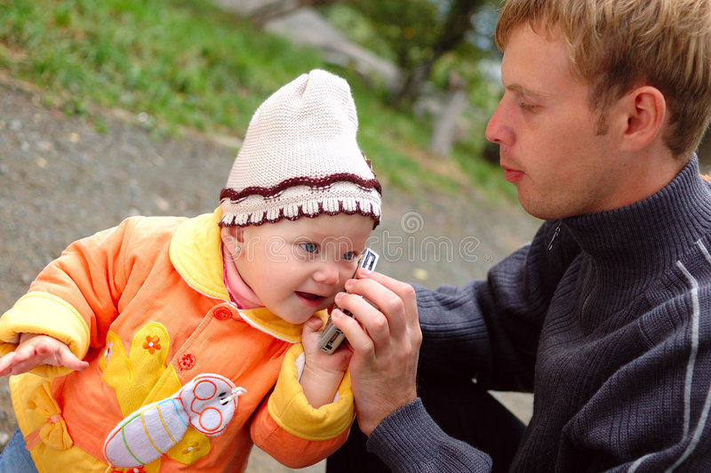 Father And Daughter Talk On Mobile Phone. Royalty Free Stock Photo