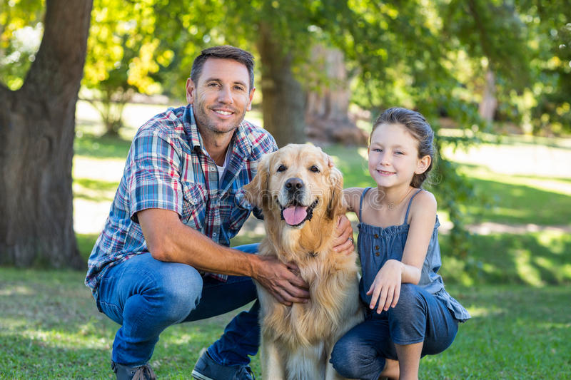 Father and daughter with their pet dog in the park stock photo
