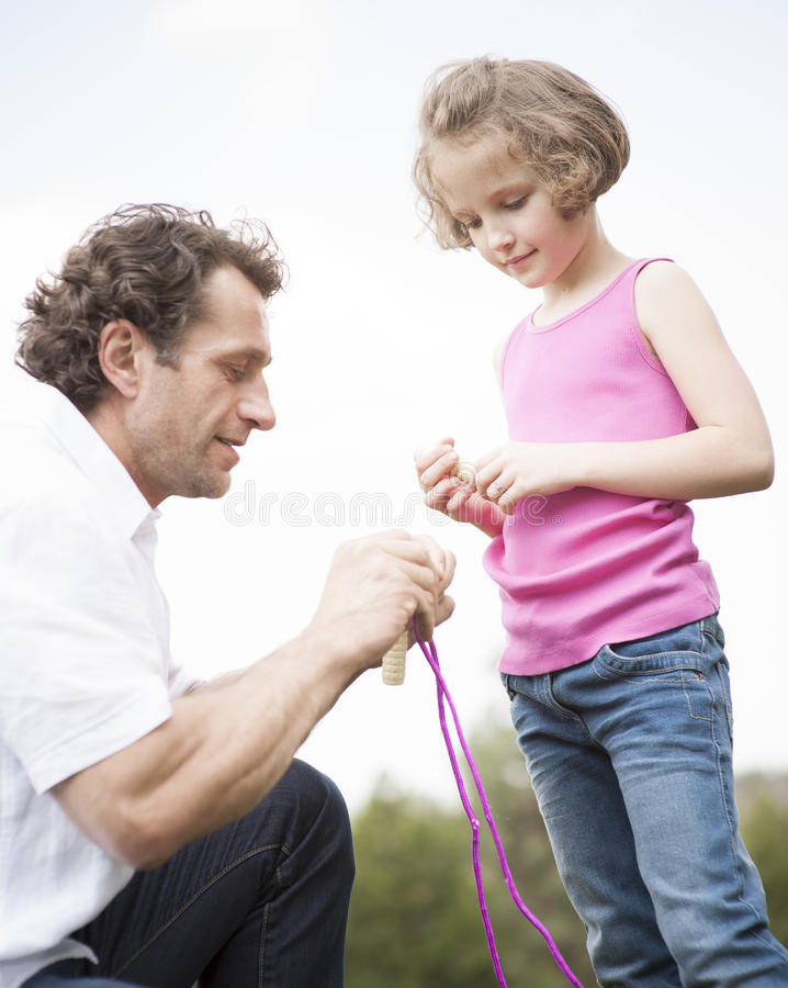 Father and daughter together with skipping rope stock image