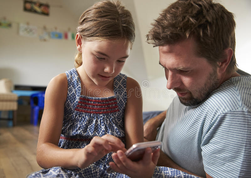 Father And Daughter Using Mobile Phone In Playroom Together stock images