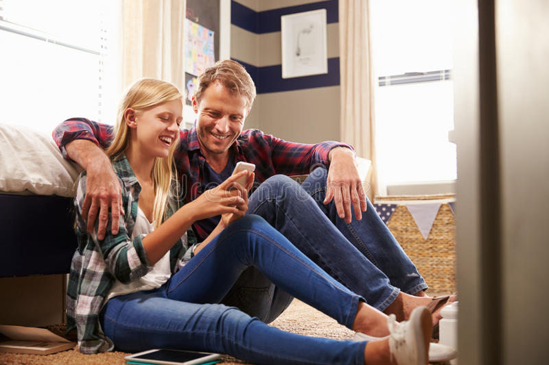 Father and daughter using smart phone together stock photo