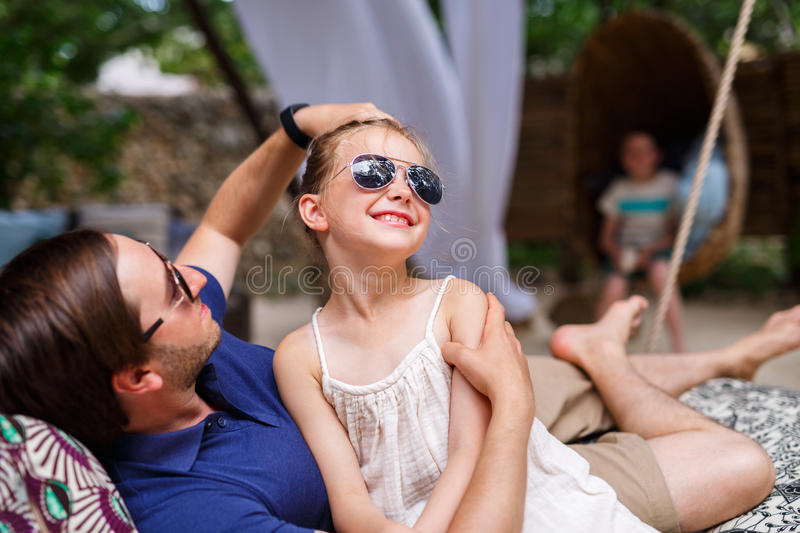 Father and daughter on vacation. Father and daughter relaxing in hammock stock photo