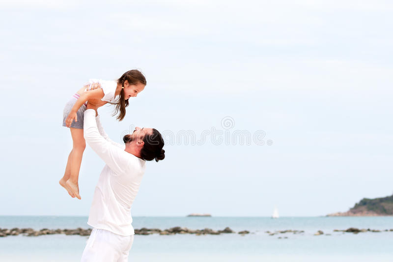 Father and daughter walking on deserted tropical beach together happy loving vacation royalty free stock photography