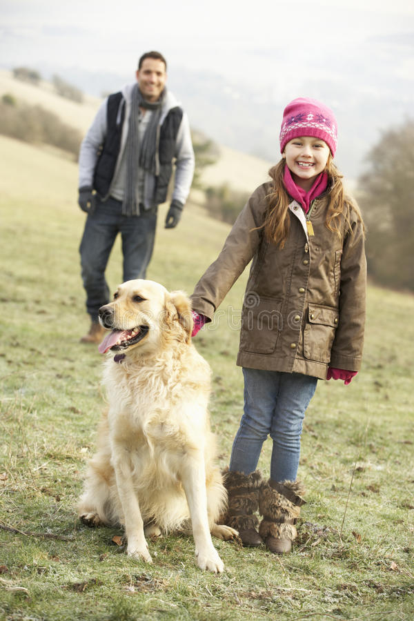 Father and daughter walking dog in country royalty free stock photos