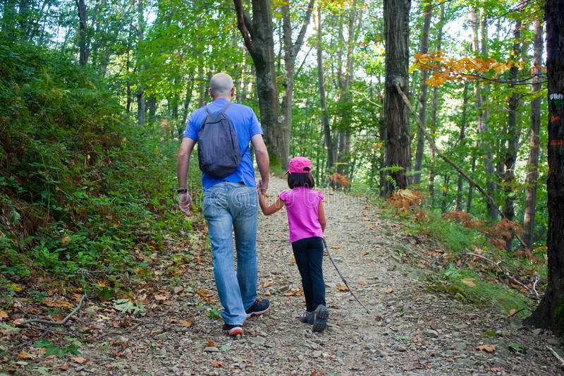 Father and daughter walking in the forest royalty free stock image