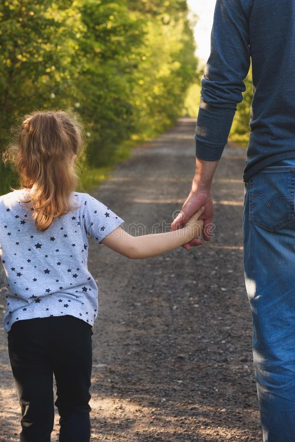Father and daughter walking in the park holding hands. We will love and take care of you forever concept stock photography