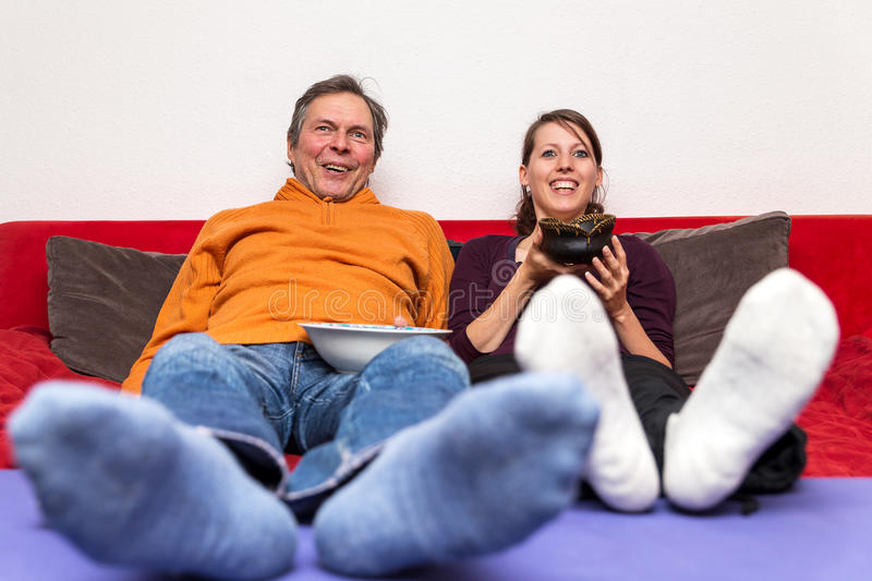 Father and daughter watching a funny movie. Father and daughter on a couch watching a funny movie stock images
