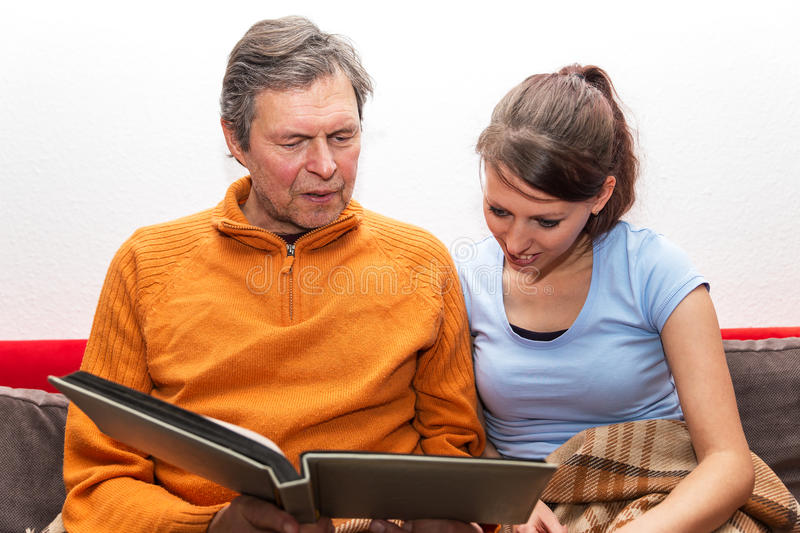 Father and daughter watching photos. Father and daughter are watching a photo album stock photography
