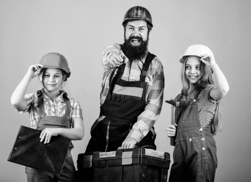 Father and daughter in workshop. Family teamwork. Repair. Repairman in uniform. Engineer. Bearded man with little girls stock photos