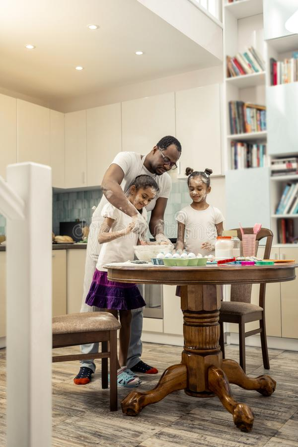 Father and daughters cooking in the morning in spacious kitchen. Spacious kitchen. Father and daughters cooking in the morning in light and spacious kitchen stock photography