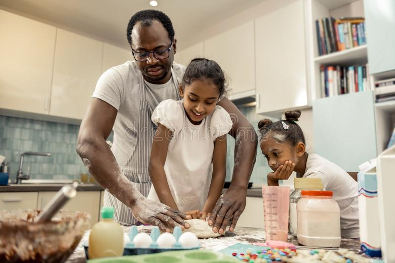 Father and daughters enjoying their traditional morning while cooking. Traditional morning. Loving father and daughters enjoying their traditional morning while royalty free stock photography