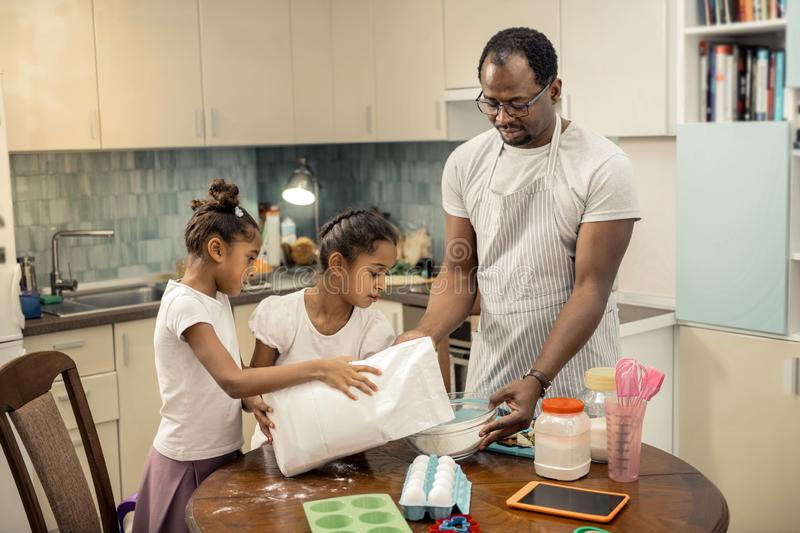 Father and daughters feeling involved in cooking pie together. Cooking pie together. Loving father and cute daughters feeling involved in cooking pie together royalty free stock photo