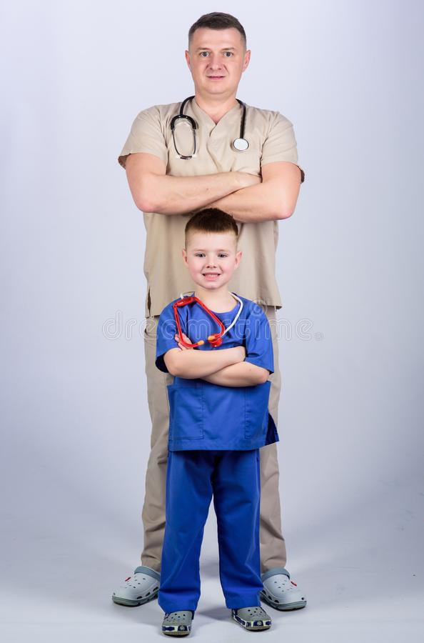 Father doctor with stethoscope and little son physician uniform. Medicine and health care. Future profession. Want to be. Doctor as dad. Cute kid play doctor royalty free stock photos