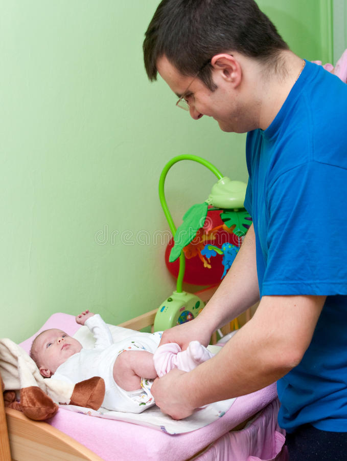 Father dressing baby royalty free stock image