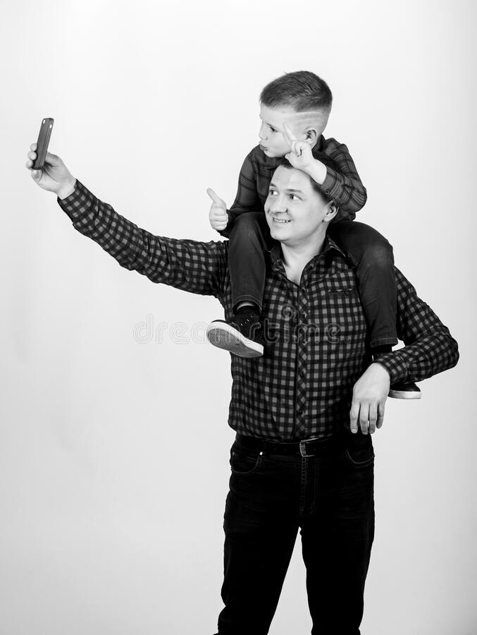 Father example of noble human. Father little son red shirts family look outfit. Taking selfie with son. Child riding on. Dads shoulders. Happiness being father royalty free stock images