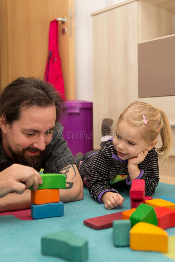 Father exhibiting bricks to his daughter stock photography