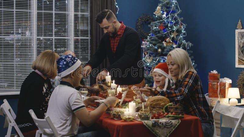 Man carving turkey on Christmas dinner stock image