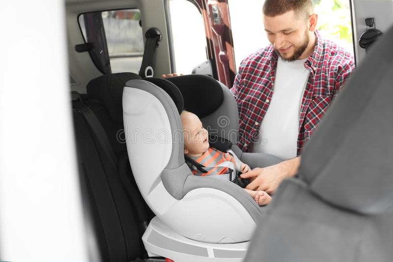 Father fastening baby to child safety seat inside royalty free stock photo