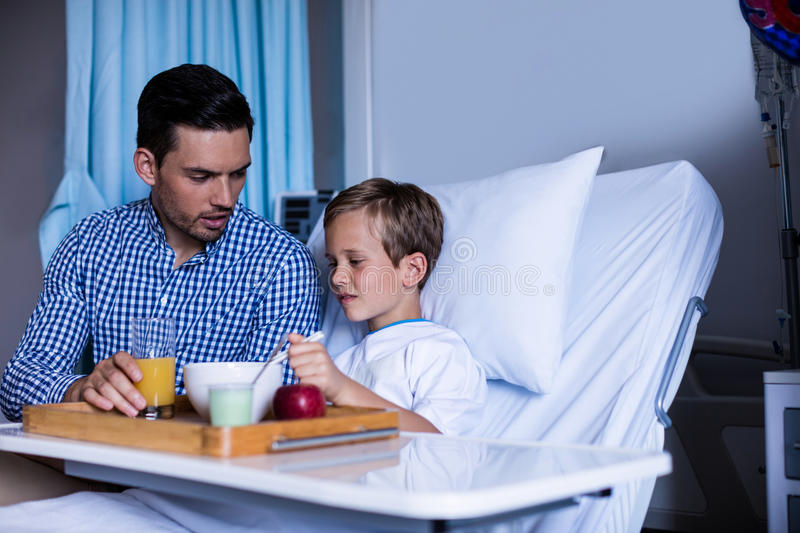 Father feeding breakfast to his son royalty free stock images
