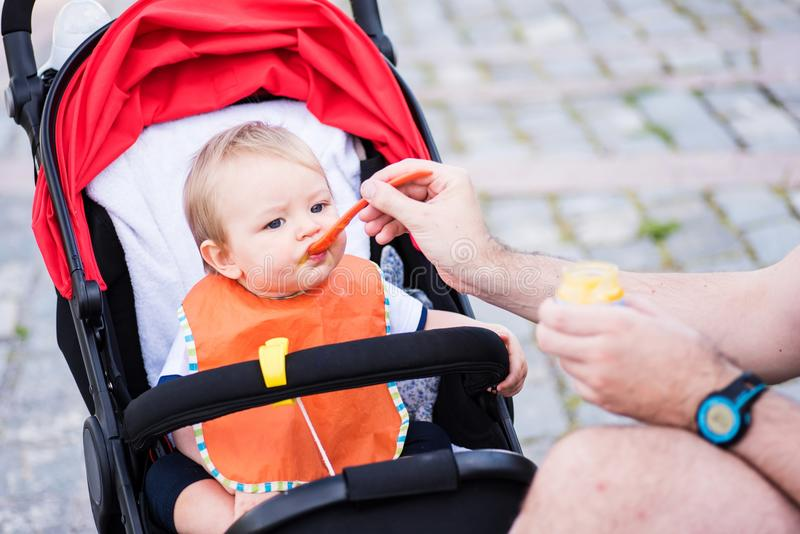 Father feeding his baby boy in the park stock photography