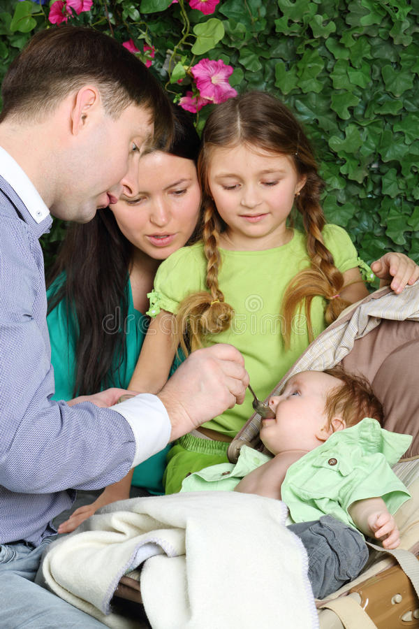 Father feeds baby, mother and daughter look at baby in garden stock image