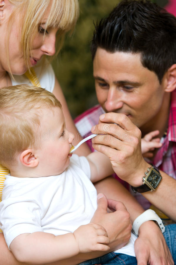 Father feeds baby son stock photo