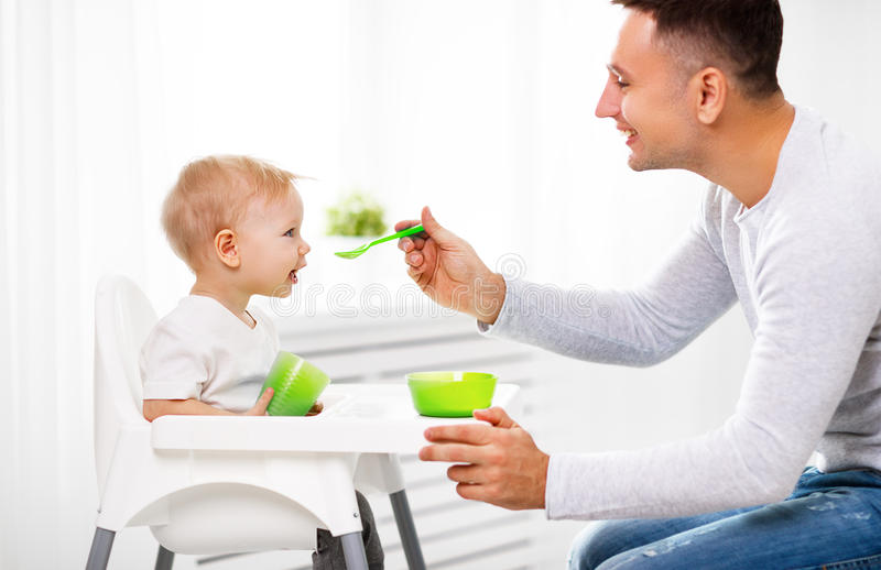 Father feeds baby from spoon stock image