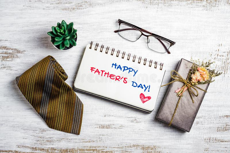 Father' feliz; concepto del día de s Imagen puesta plana de la caja de regalo, de la corbata, de vidrios y del cuaderno con  fotos de archivo