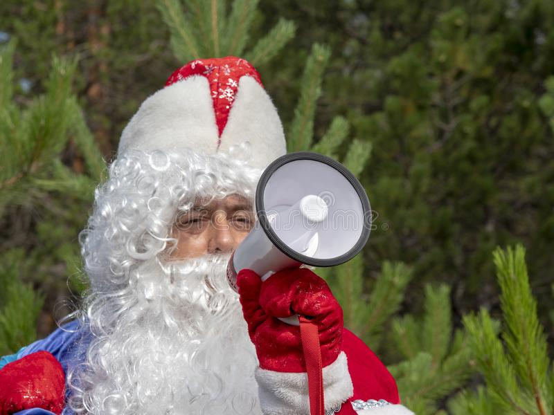 Father Frost shouts in the megaphone. The New Year`s character informs in a loud-hailer against the background of the nature royalty free stock images