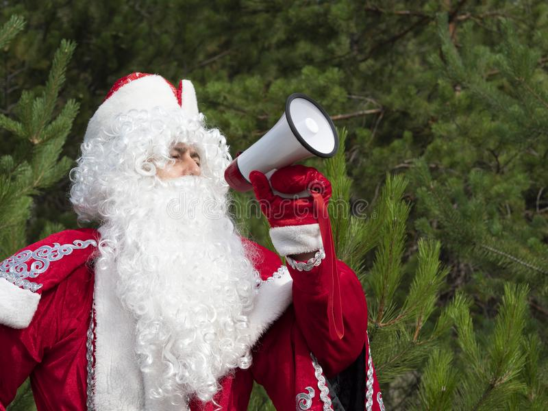 Father Frost shouts in the megaphone. The New Year`s character informs in a loud-hailer against the background of the nature royalty free stock photography