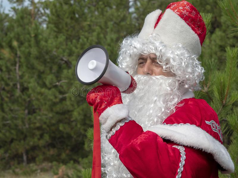 Father Frost shouts in the megaphone. The New Year`s character informs in a loud-hailer against the background of the nature stock photo