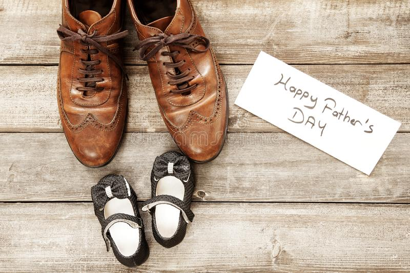 Father and girl brown shoes on wooden background, fathers day stock photography