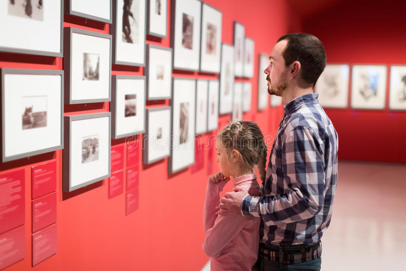 Father and girl exploring exhibition of photos royalty free stock image