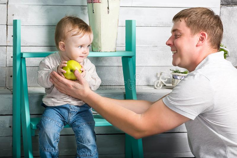 Father gives to baby boy big green apple. He both are in jeans and white hoodie.  Dad with son sits on the steps indoor. White royalty free stock photos
