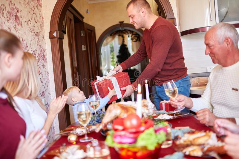 Dad giving a red gift to little son on a festivebackground. Family Christmas presents concept. Father giving a big red present box to his happy son next to stock photography