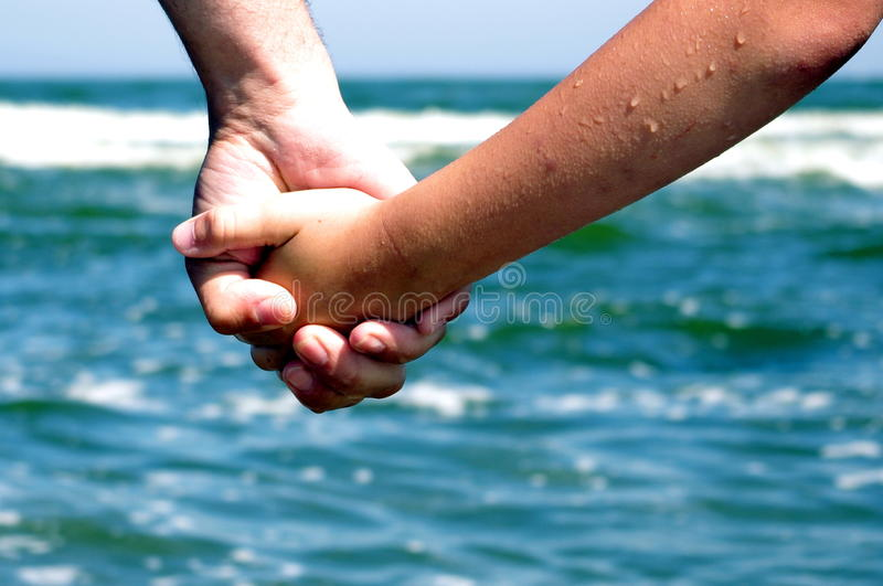 Father giving hand to a child ocean sea background royalty free stock photography
